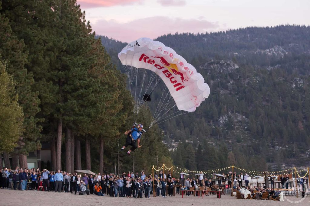 Red bull parachute skydiver on a beach at Lake Tahoe, California. Lake Tahoe corporate photographer and commercial photographer Drew Bird.