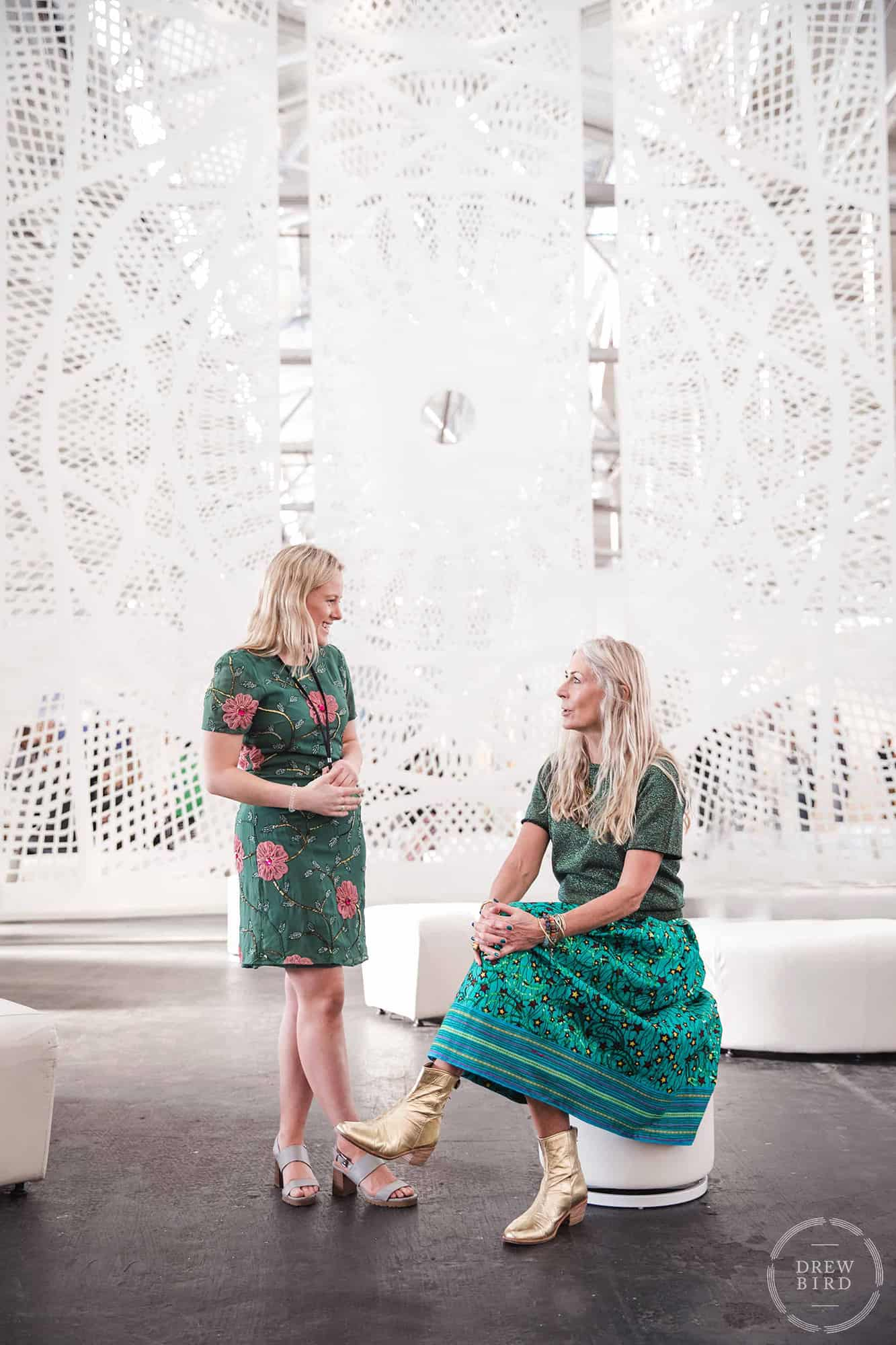 Two attractive women with blond hair and green dresses talking at Fort Mason festival pavilion. San Francisco corporate lifestyle and event photographer Drew Bird.