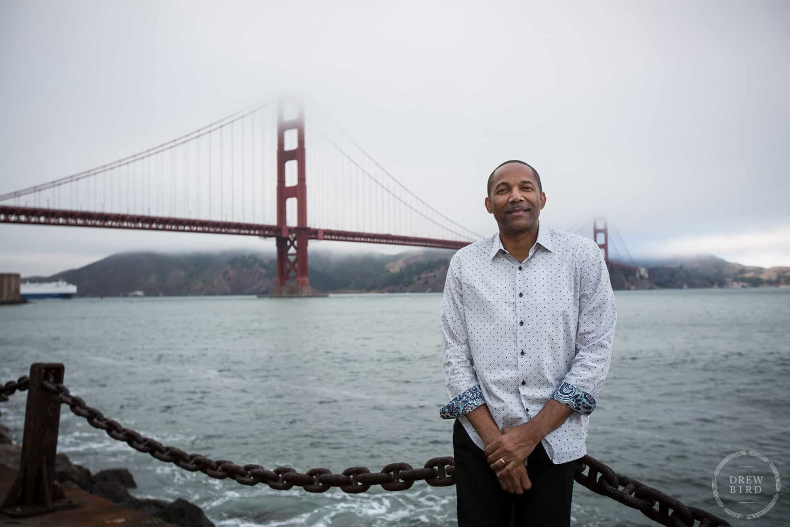 A man leans on a chain fence with Golden Gate Bridge. San Francisco editorial portrait photographer Drew Bird.