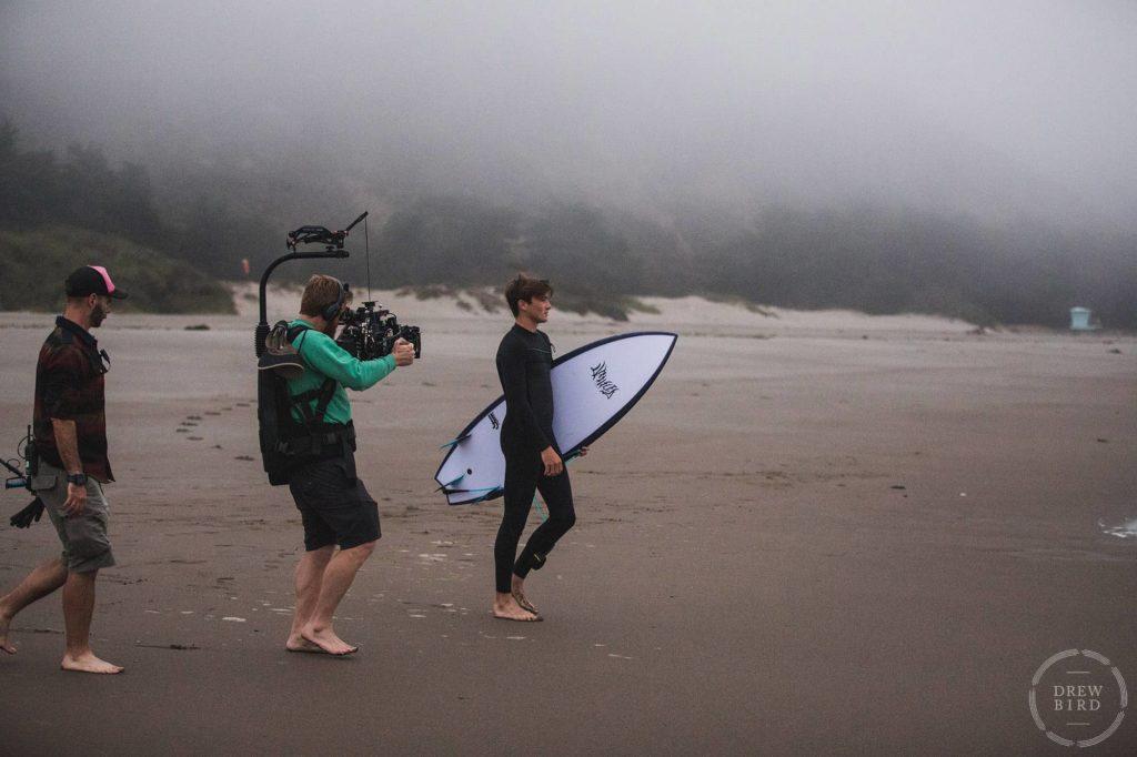 Film crew filming a man with a surfboard on beach in Stinson Beach. San Francisco movie set unit still photographer Drew Bird