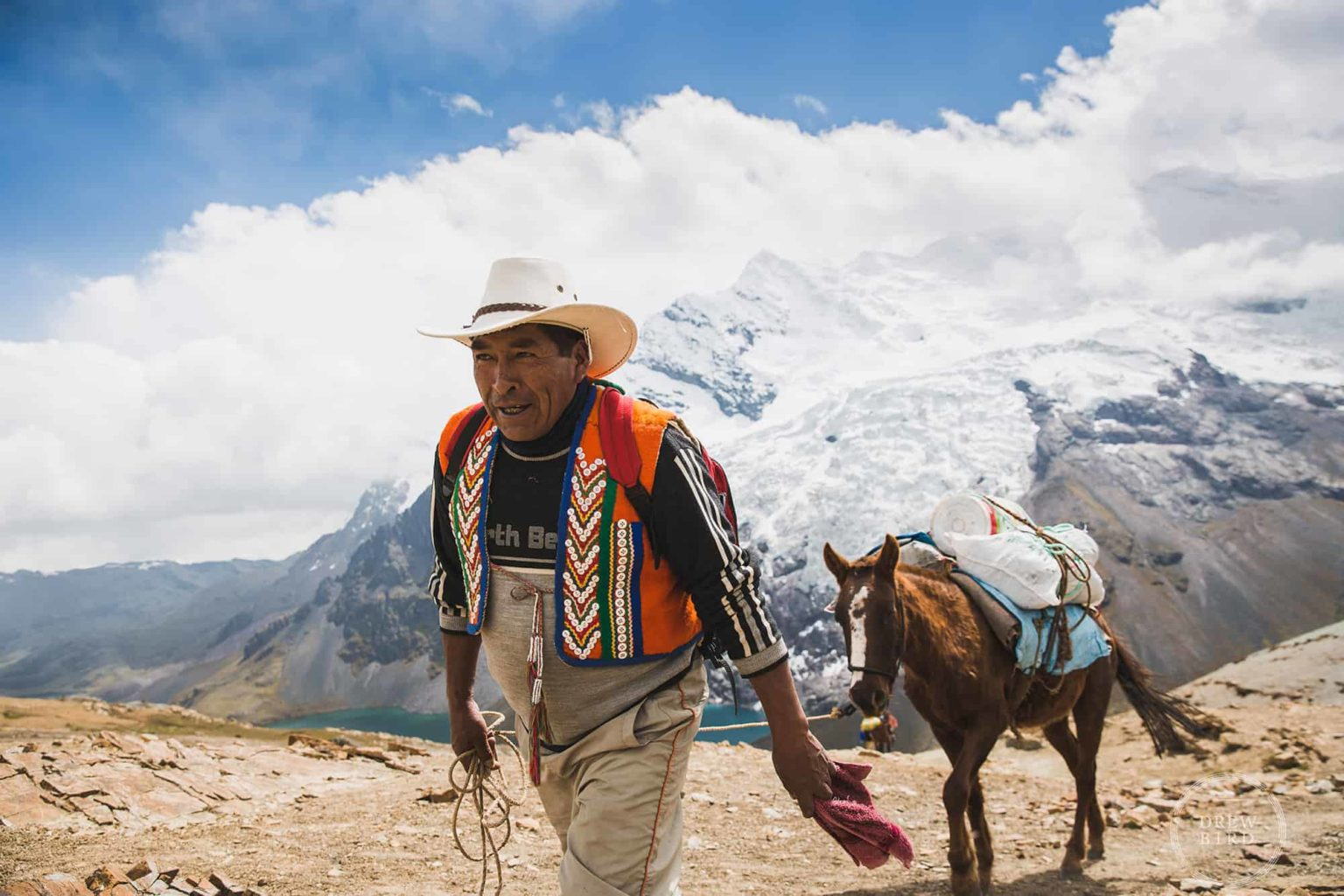 A mountain guide leads a pack horse with Ausangate tropical glacier in background in the mountains of Peru. San Francisco Editorial Photographer Drew Bird.