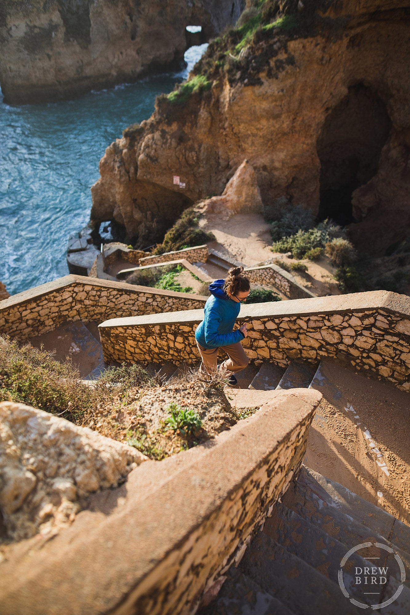 Woman running up stone stairs in Portugal wearing Patagonia jacket. San Francisco brand and commercial photographer Drew Bird.
