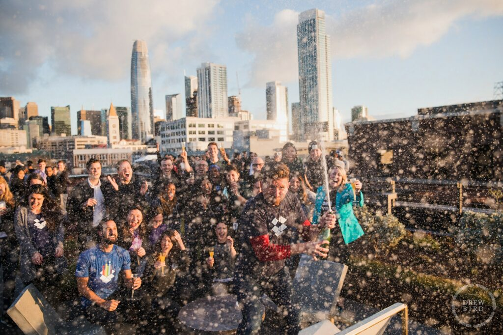 Dropbox IPO corporate lifestyle photo project. Champagne celebration at sunrise on the rooftop garden at Dropbox HQ with San Francisco skyline. Commercial photographer Drew Bird.