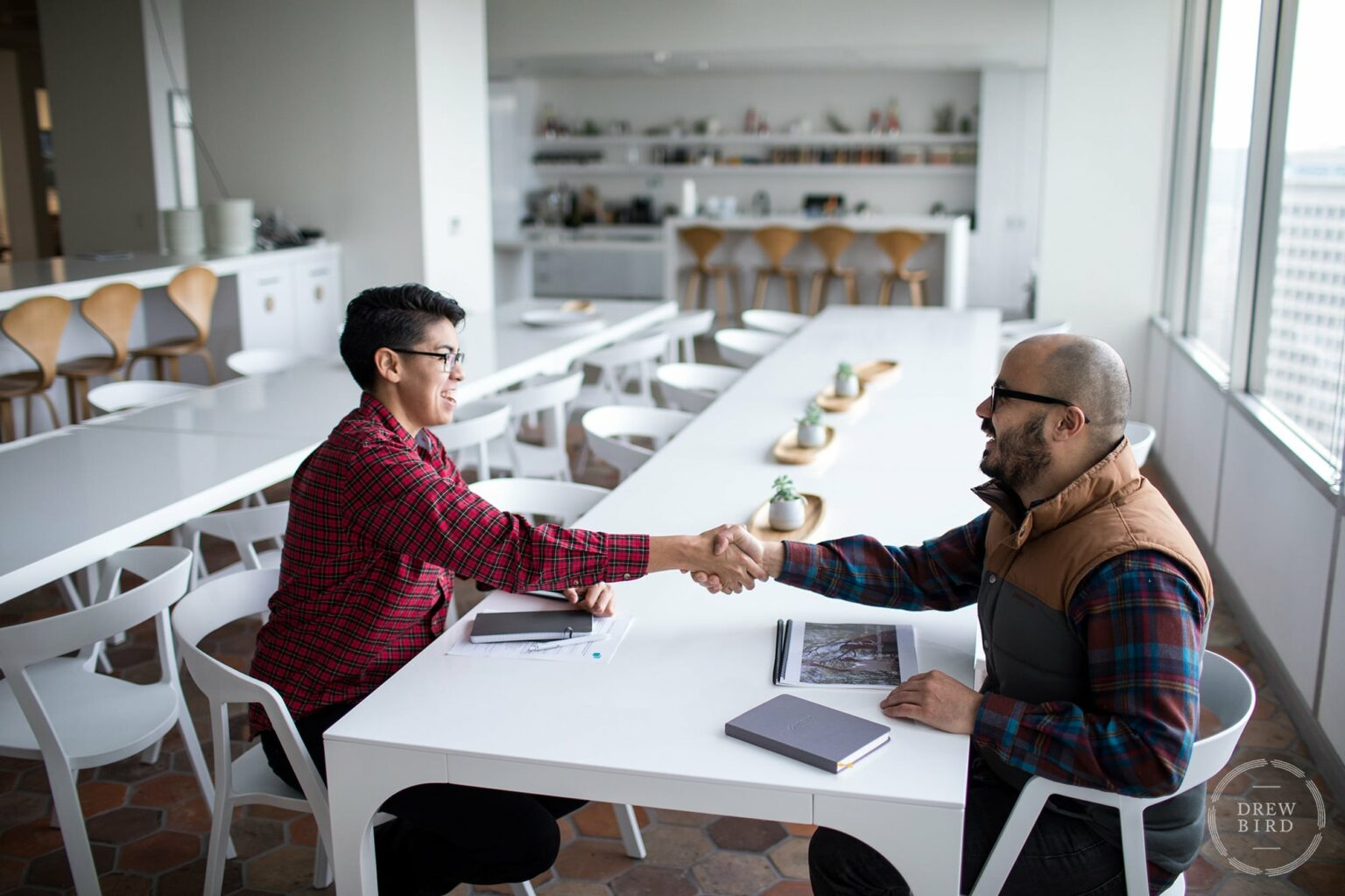Two men shaking hands in corporate office. San Francisco corporate lifestyle photographer Drew Bird.