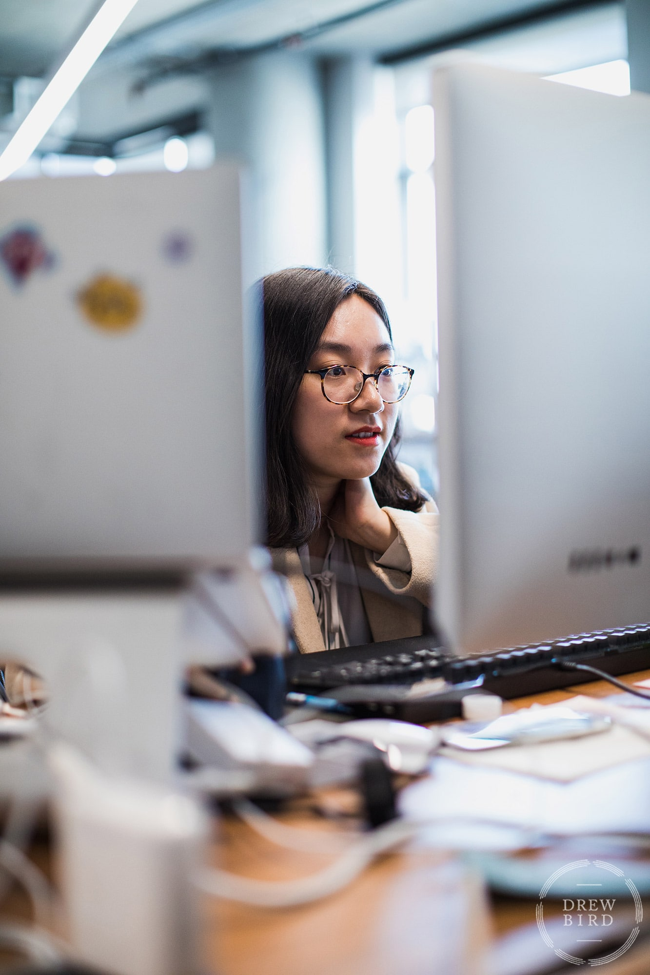 Woman with glasses working at a computer at Dropbox. San Francisco corporate lifestyle photographer Drew Bird.