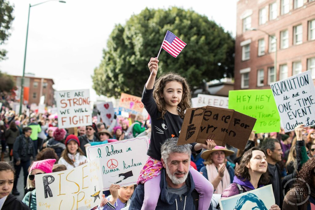 """Women's March public demonstration. A little girl sits on her father's shoulders with a protest sign that reads """"peace for everyone."""" Oakland editorial photographer Drew Bird."""
