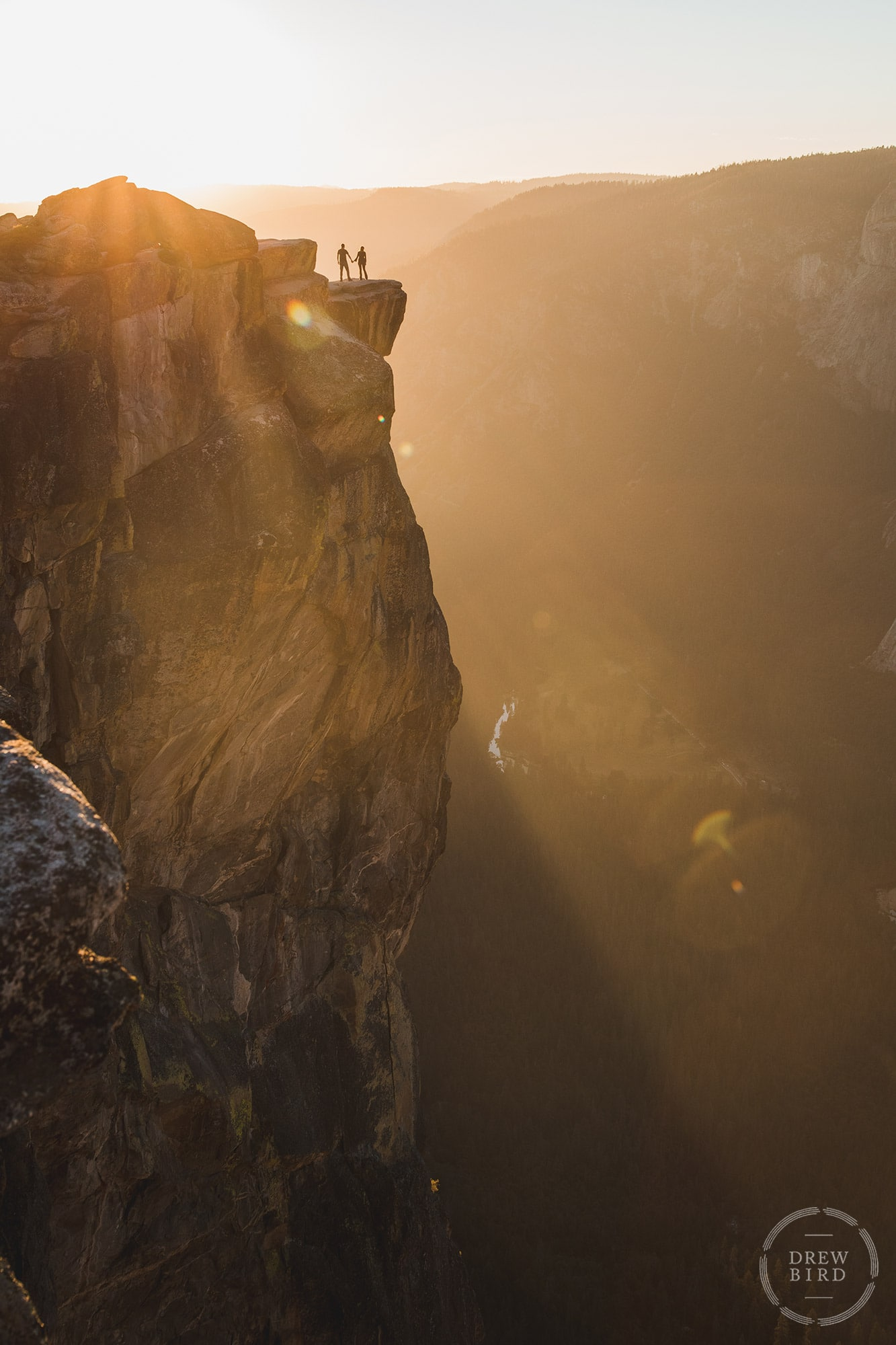 Silhouette of a couple holding hands on Taft Point in Yosemite National Park at Sunset. San Francisco brand and commercial photographer Drew Bird.