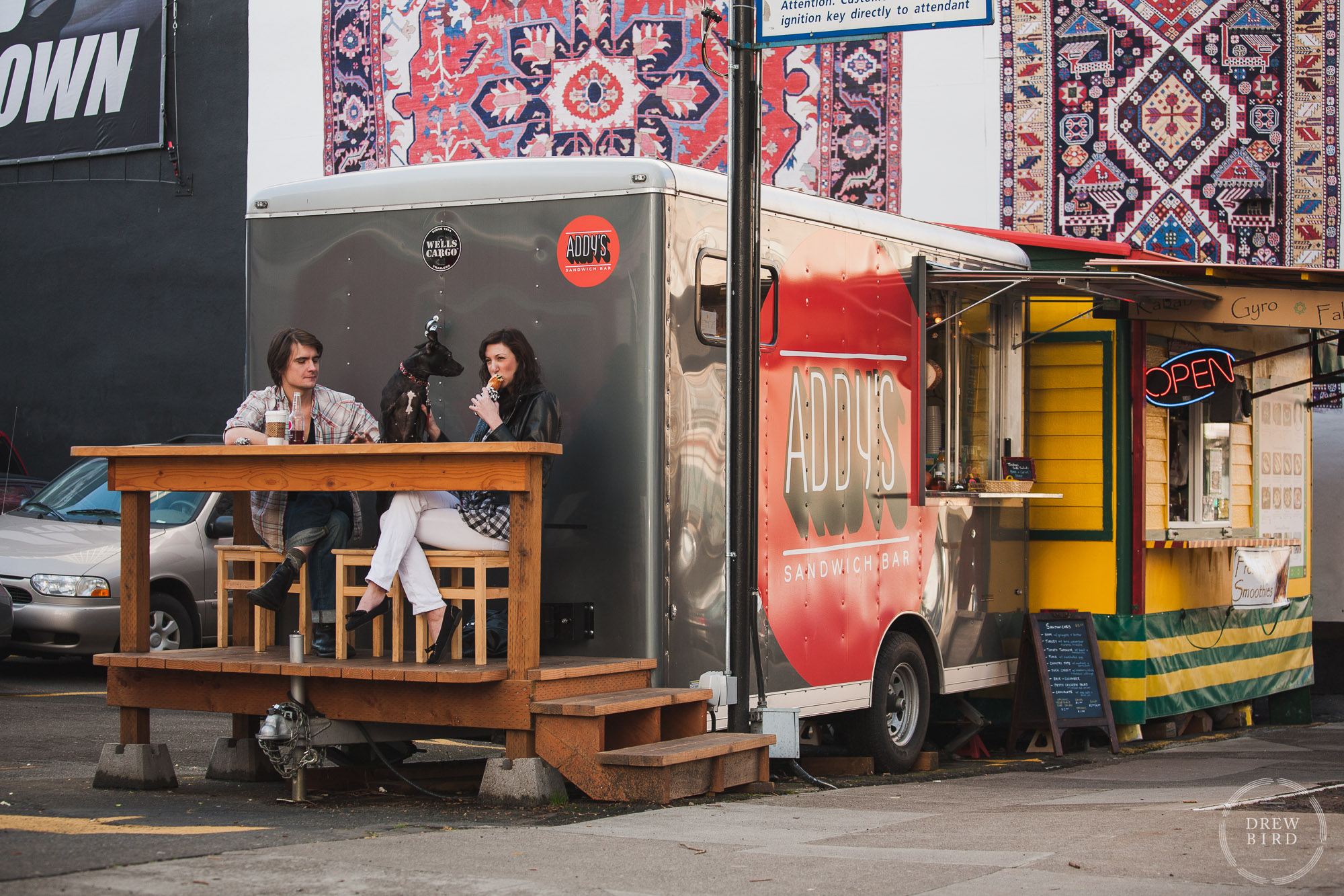 Portland Oregon food carts. Addie's sandwiches with a man and woman eating on a raised deck.